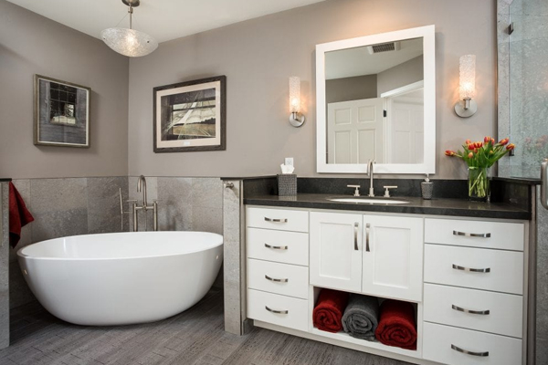 Bathroom with white cabinet, grey walls, and a stand-alone tub