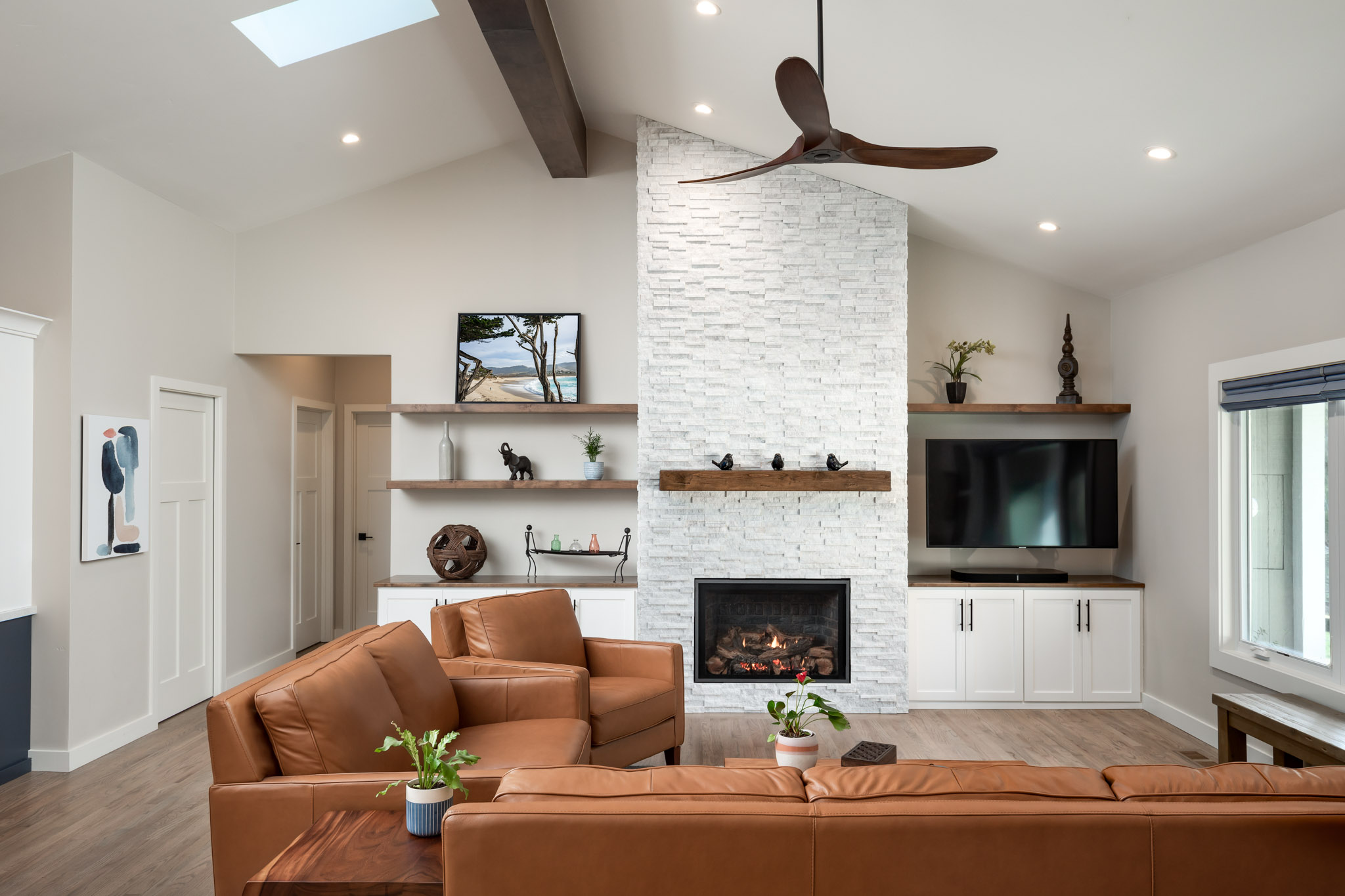 White stone fireplace with contrasting brown leather couch