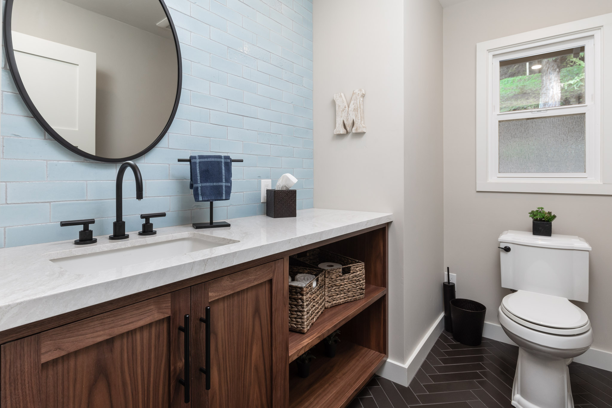 Bathroom counter with white marble top and contrasting black mirror