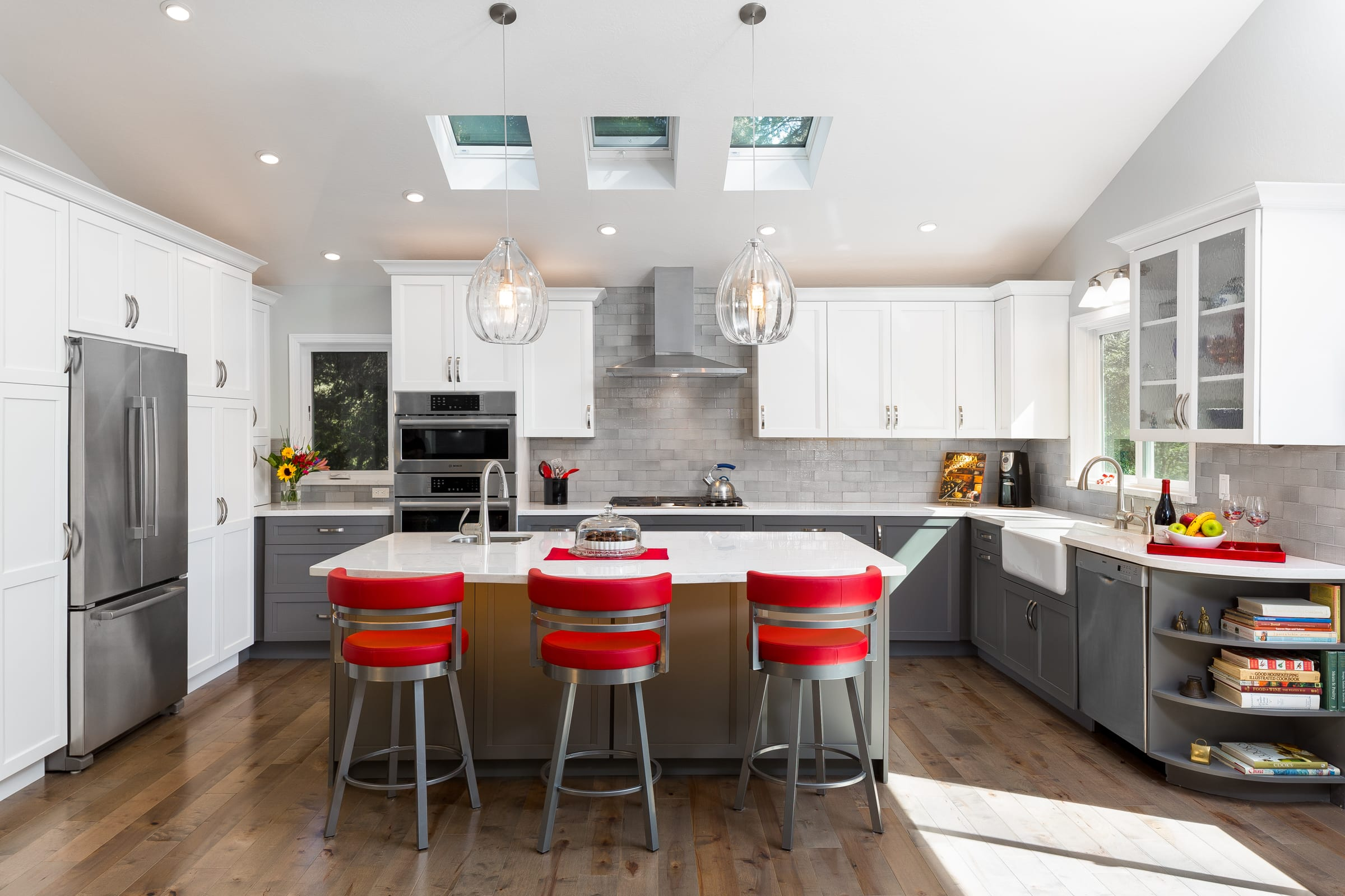 After kitchen remodel with three skylights, red barstools, and white cabinetry