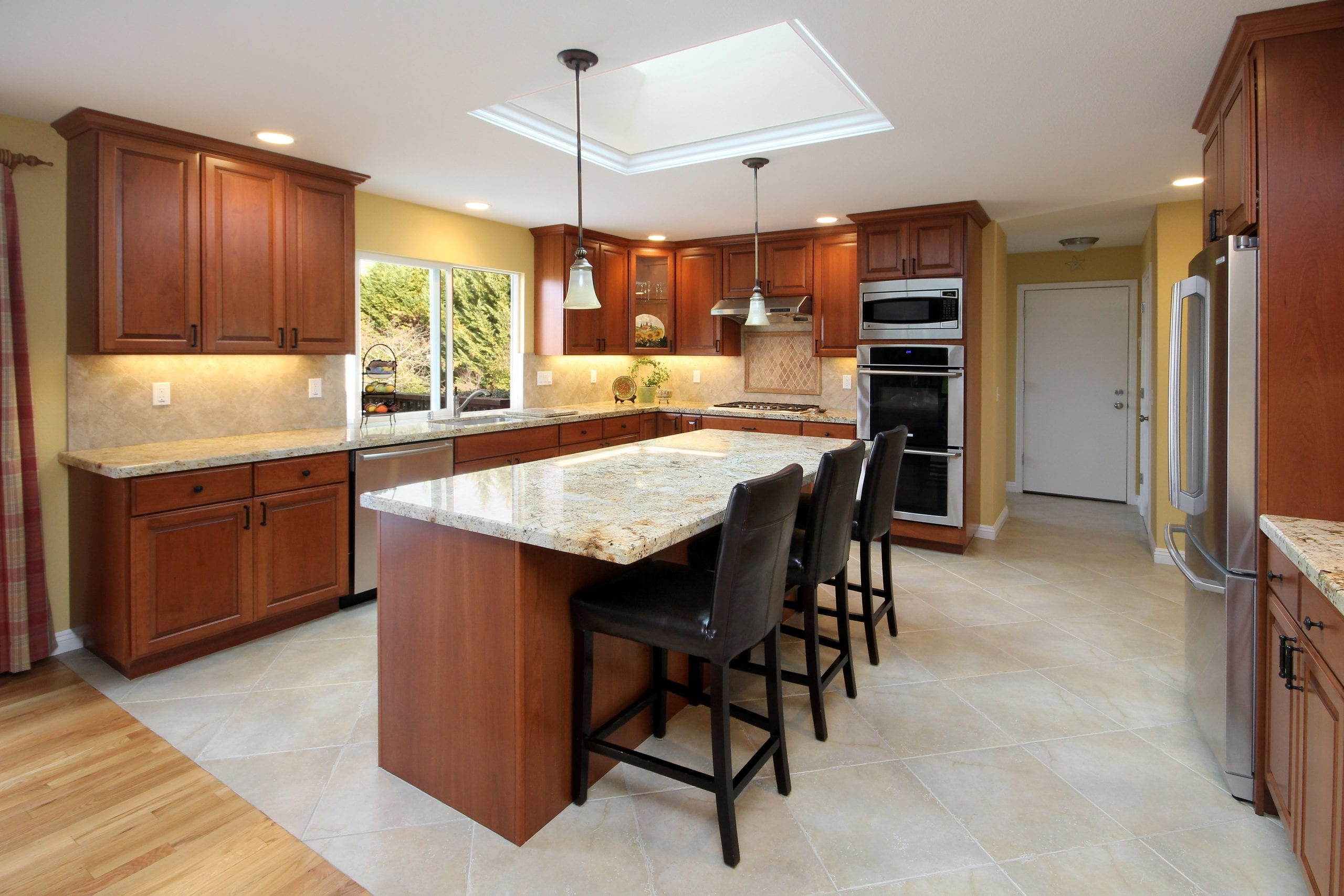 Kitchen remodel after photo showcasing finished cabinets, a stand-alone island, and a skylight