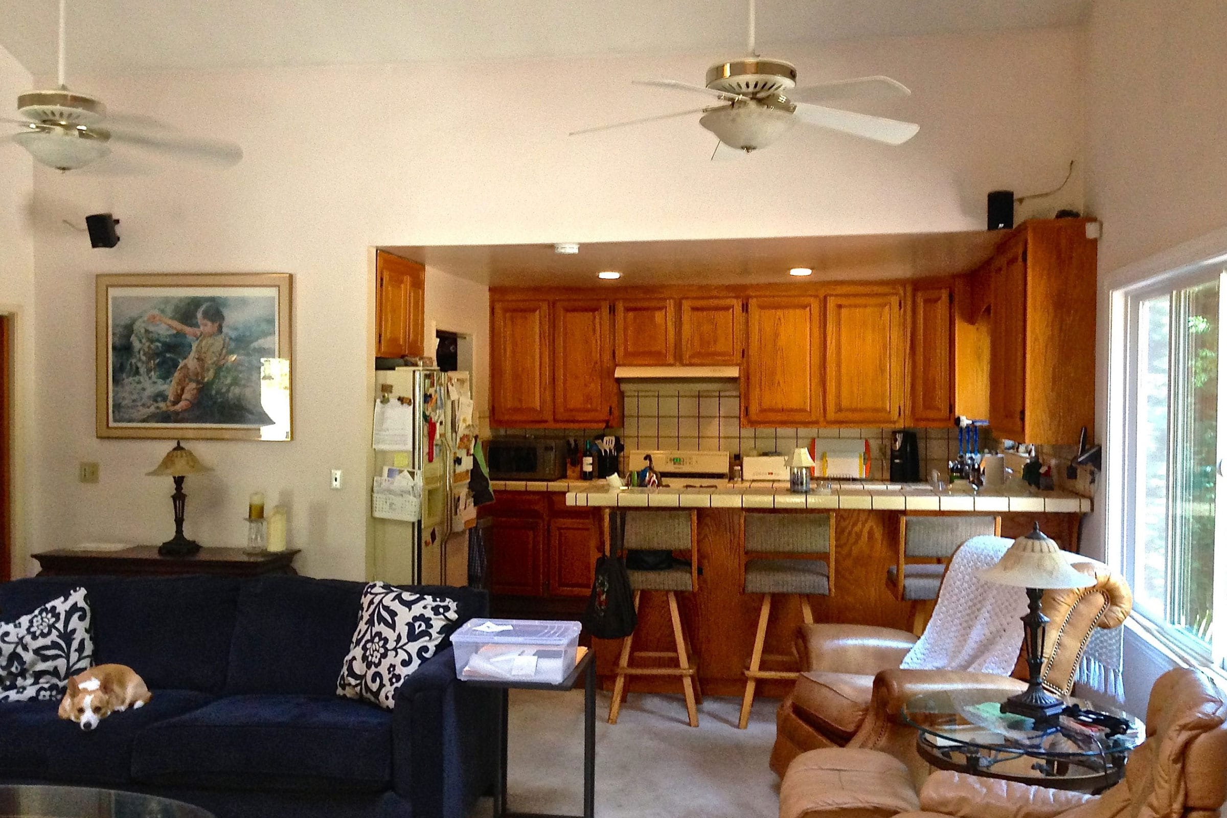 Before kitchen remodel with two ceiling fans and wooden cabinets