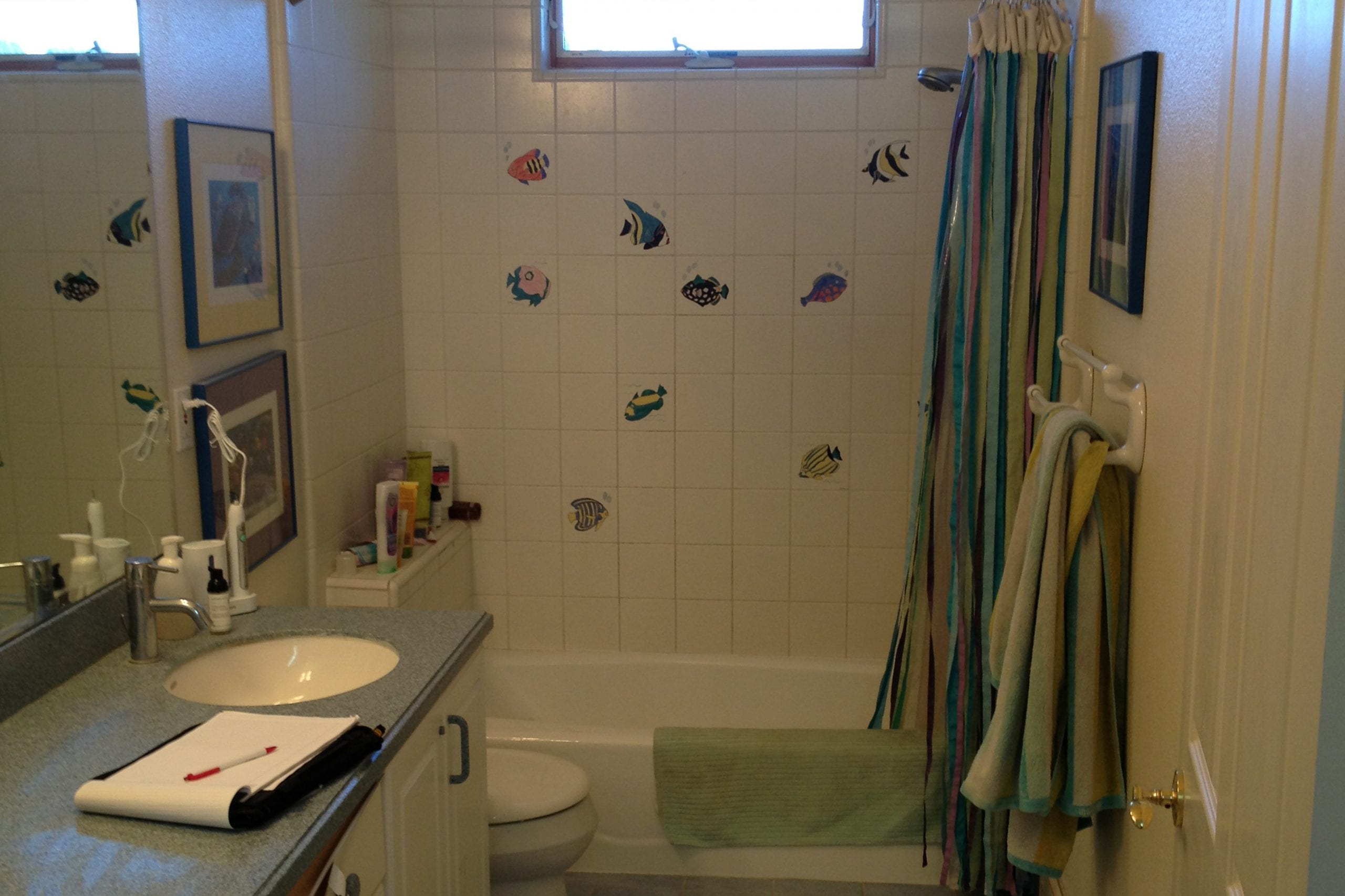 Bathroom with dim lighting, white tile, and fish stickers on the walls