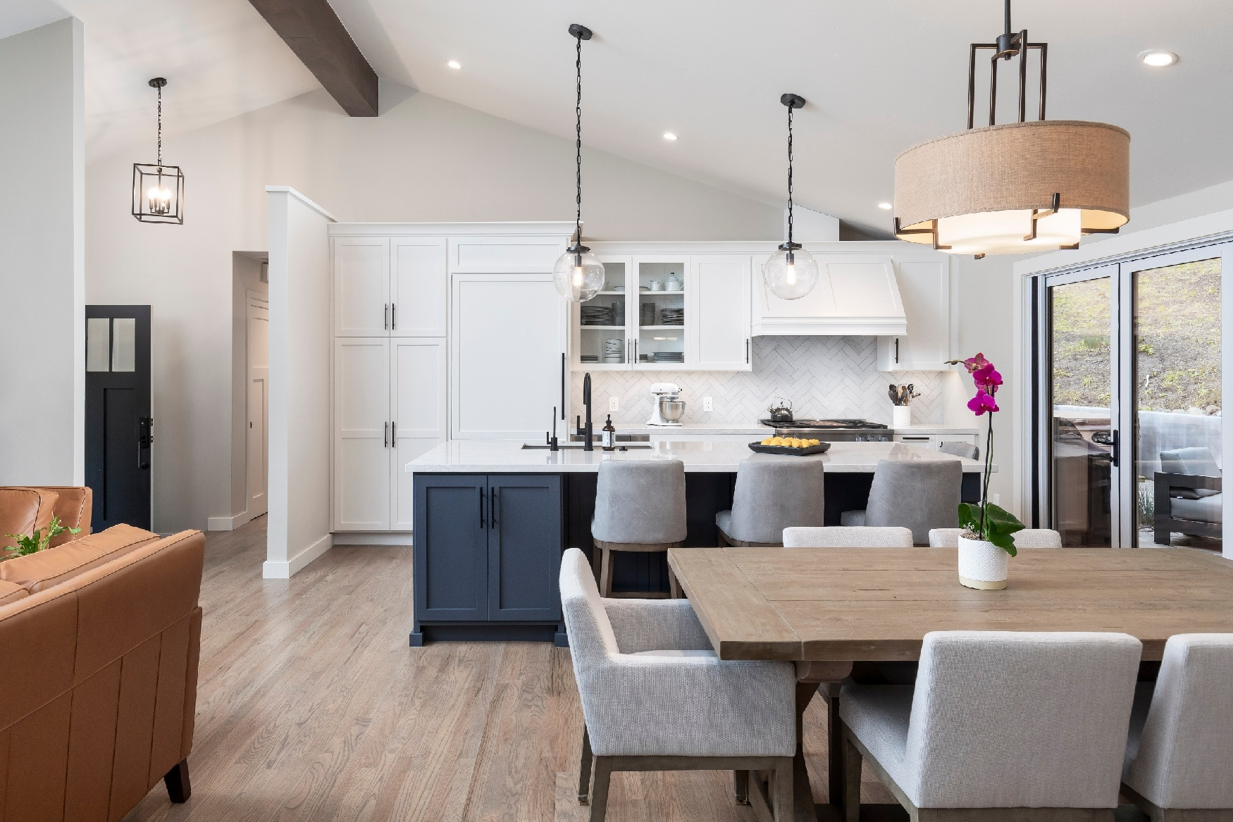 Inviting kitchen and dining area with tan hanging lights and black countertops