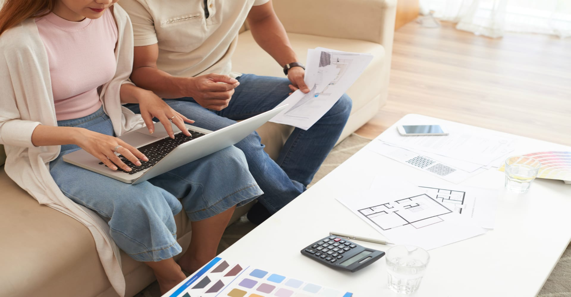 Two people reviewing a floor plan together. Hard wood floor in the background.