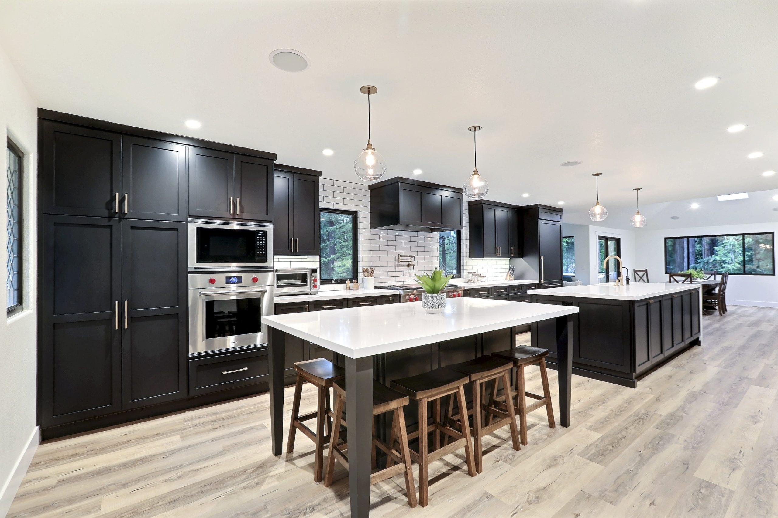 Black cabinets accent a light stained wood floor with white marble countertops