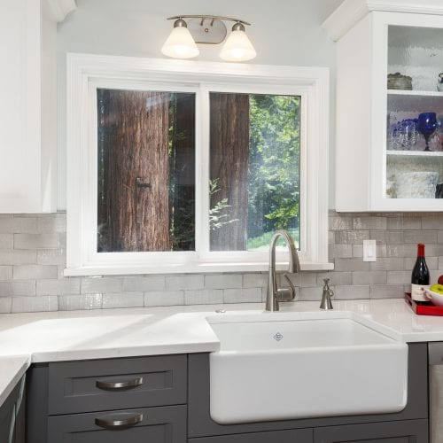White countertop and kitchen sink in front of a sliding window