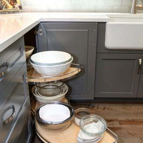 Retractable storage cabinet full of glass and ceramic bowls
