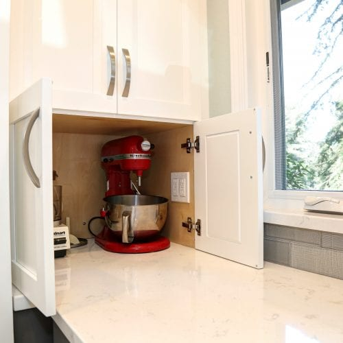 Kitchen cabinet with red stand mixer stored inside