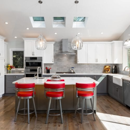 Elegant kitchen remodel with red barstools, skylights and ceiling lights