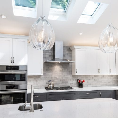 Hanging glass lamps over a white kitchen island