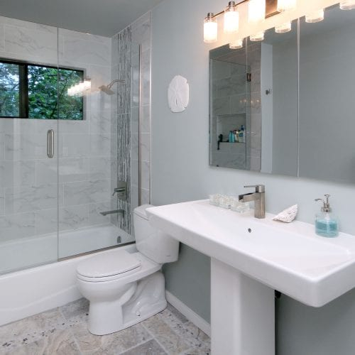 Bathroom with grey, neutral tones and a sliding glass shower door