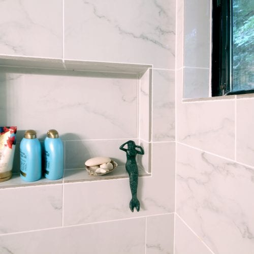 Shower shelf with a green mermaid figuring seated upon
