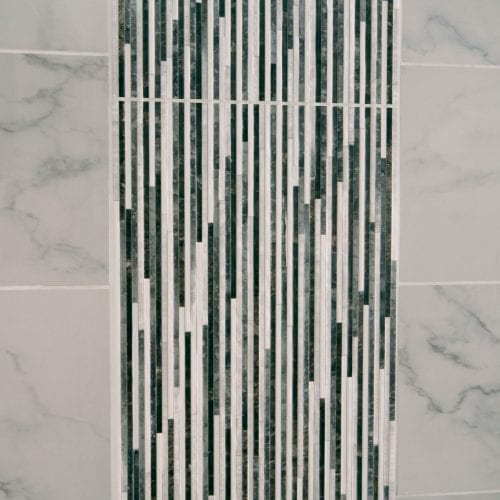 Shower tiling with a grey and white cascading effect