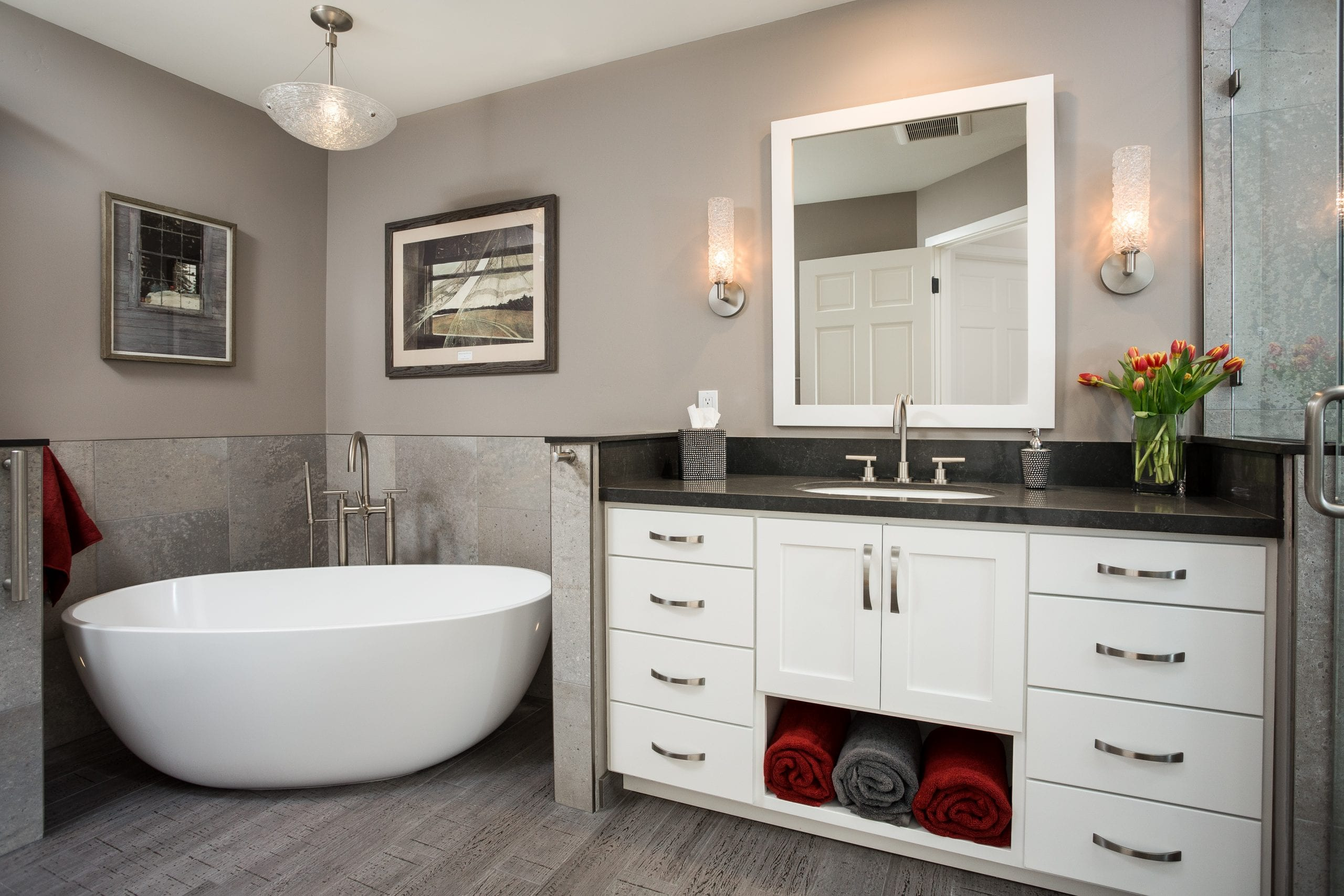 Ceramic tub next to counter with white wood cabinets