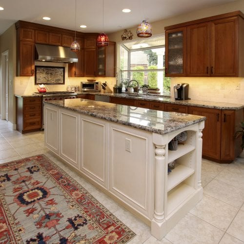 Kitchen with carpeted rug in front of island