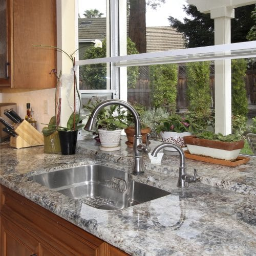 Stainless steel sink embedded into granite countertop