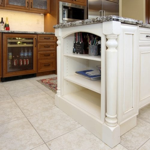 White wooden storage shelves on the end of the kitchen island