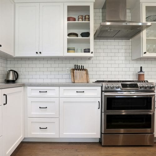 White cabinets and cupboards border metal stove and oven
