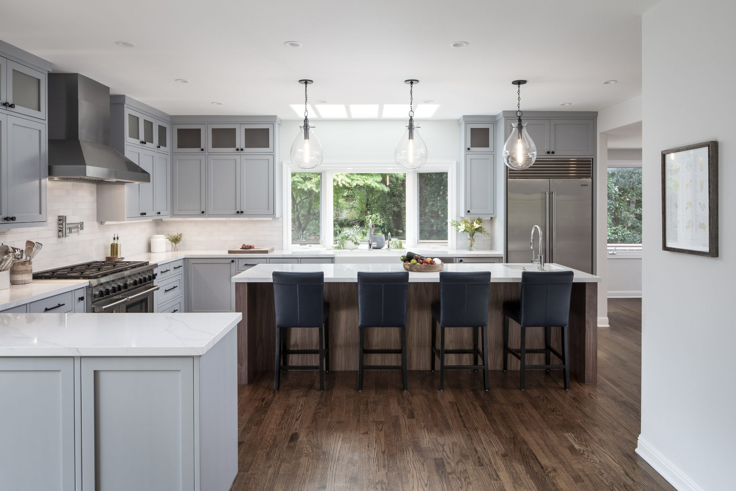Kitchen with three hanging lights over a white marble island