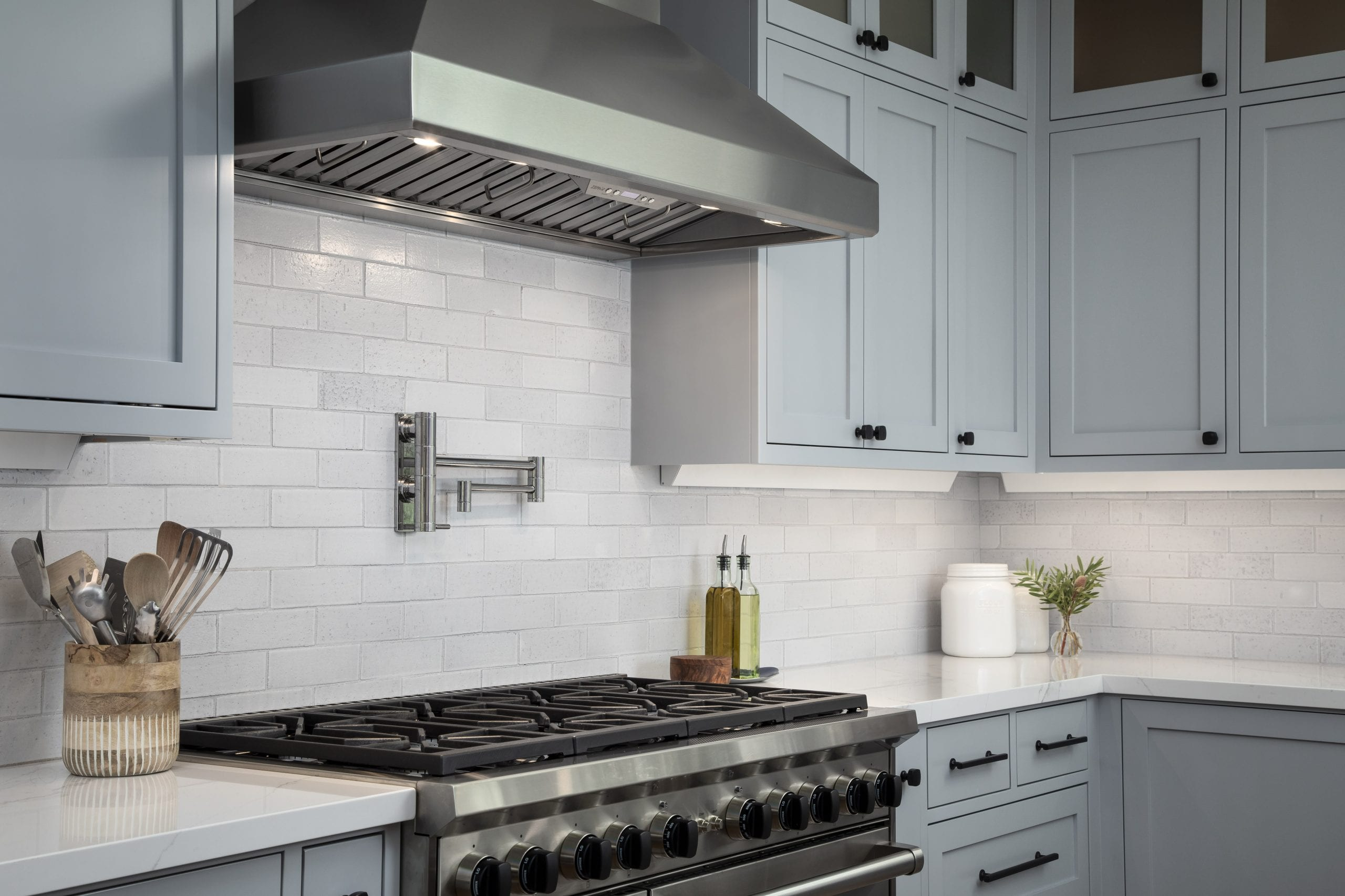 Kitchen stove with metal exhaust hood above with glass backsplash