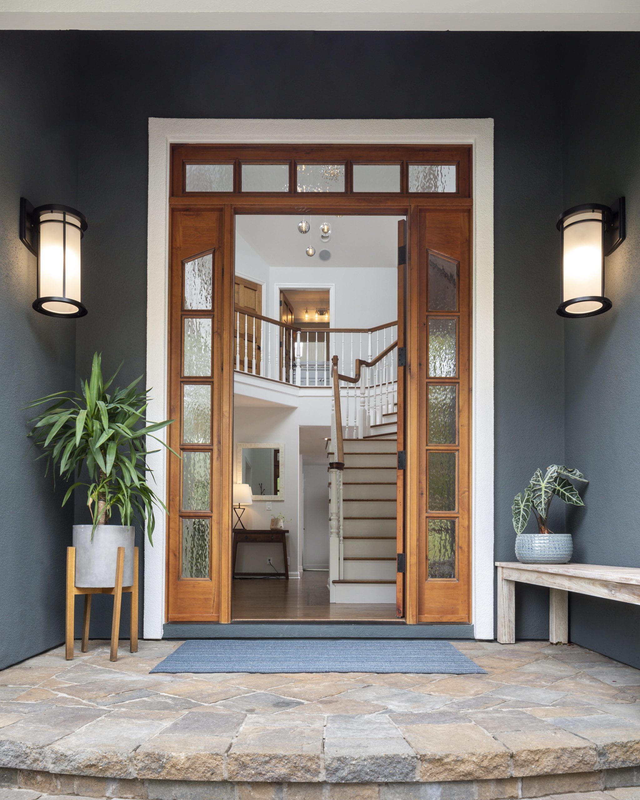 Wooden framed front door with stairway in the background