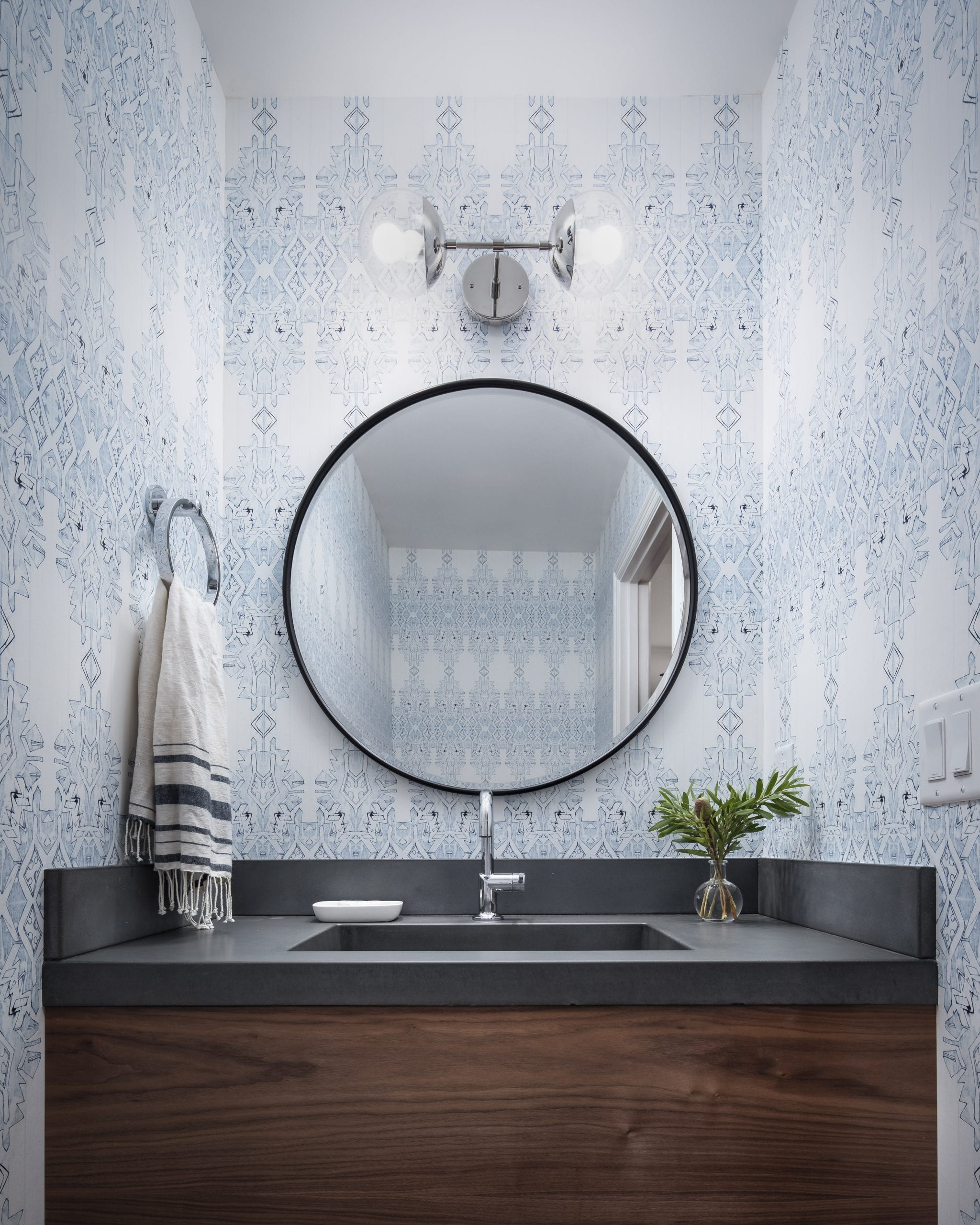 Bathroom with black circular mirror and blue and white wallpaper