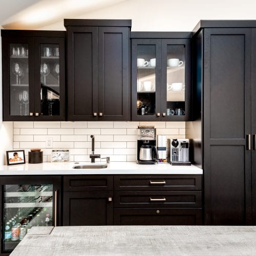 Black cabinets with white countertop and a mini refrigerator