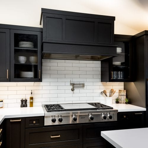 Stainless steel stove top surrounded by black finished cabinets and white tiling