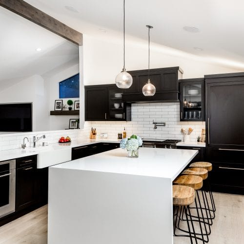 Kitchen with white stand-alone island, open wall frame, and black cabinetry