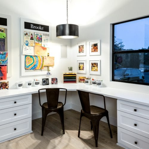 Home office with a white, L-shaped desk and 2 black office chairs