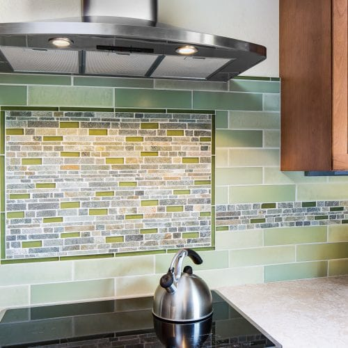 Silver teapot on electric stove in front of kitchen backsplash