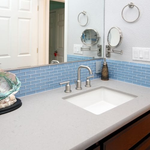 Light blue tile wall accent under large mirror