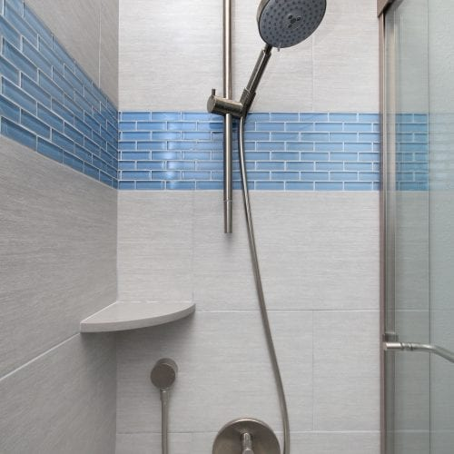 Shower with light blue tile accents and glass sliding door
