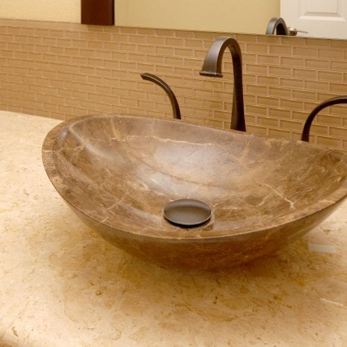 Marbled sink bowl with dark metal faucet