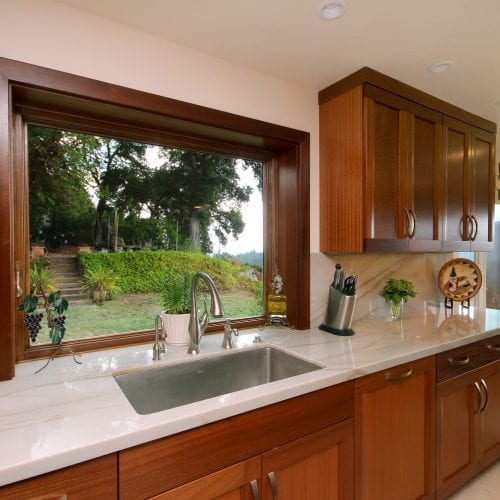 Kitchen sink in front of window overlooking trees