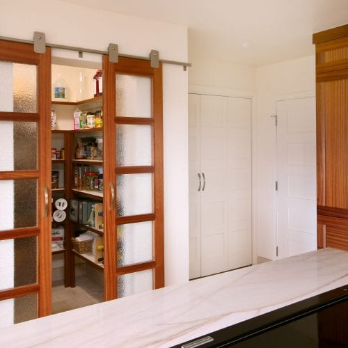 Kitchen pantry with sliding wooden doors