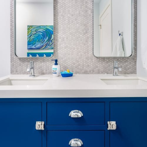 Blue wooden cabinets with dual rectangular mirrors