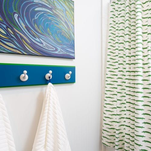 Green and white shower curtain next to blue wood towel rack