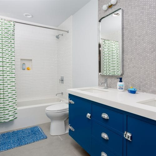 Blue cabinets in bathroom under white marble counter