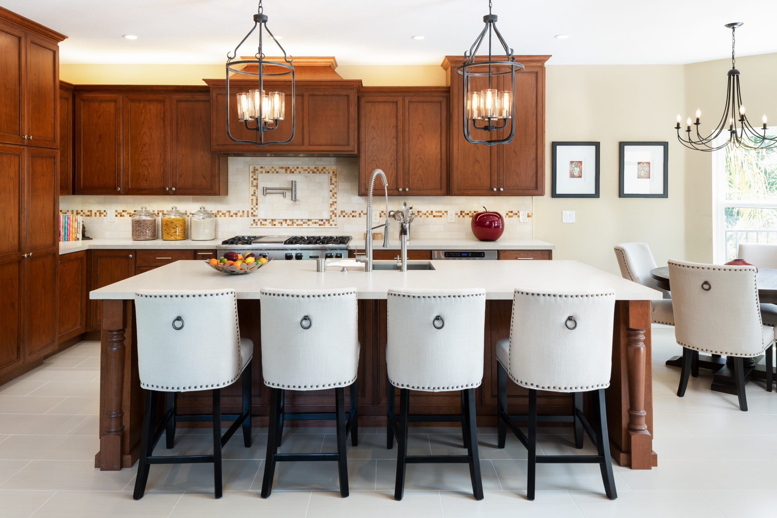 White leather high-back chairs in front of island with white marble countertop