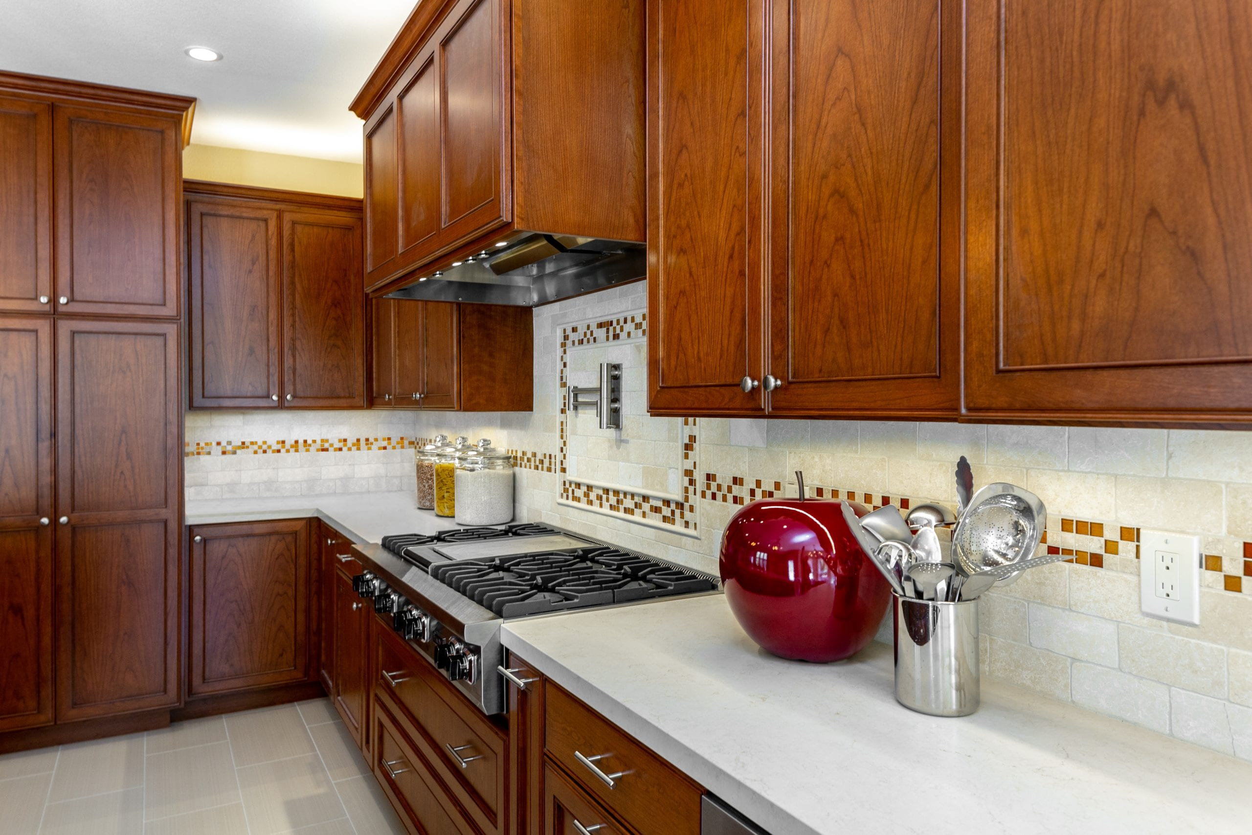 Stovetop with wood and bronze exhaust hood above