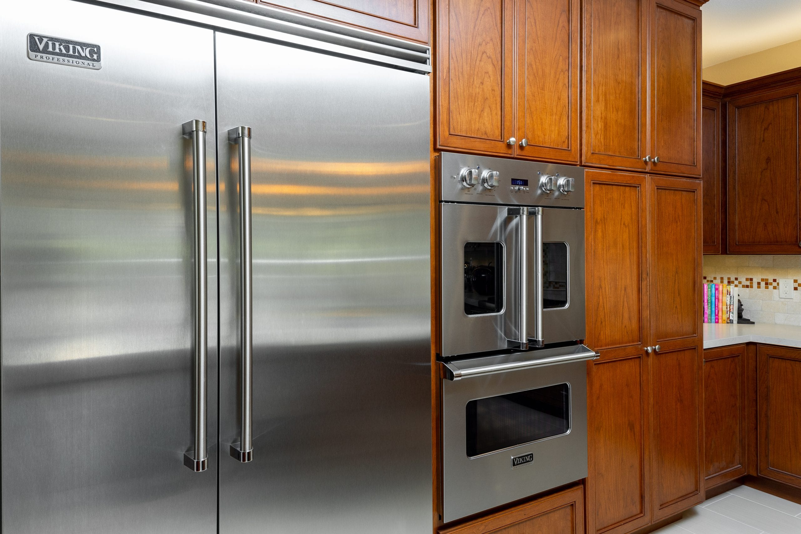 Stainless steel refrigerator next oven embedded into cabinet wall