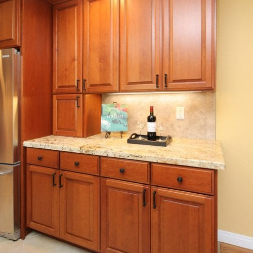 Wooden kitchen cabinets and mini-bar table next to a stainless steel fridge