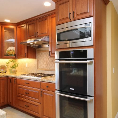 Stainless steel microwave and oven embedded in a wooden cabinet