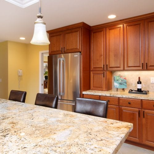 Kitchen island with granite countertop and hanging ceiling lights