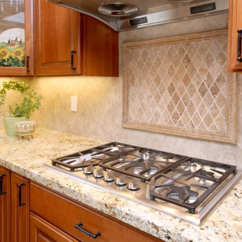 Multi-burner stove top with wooden cabinetry surrounding
