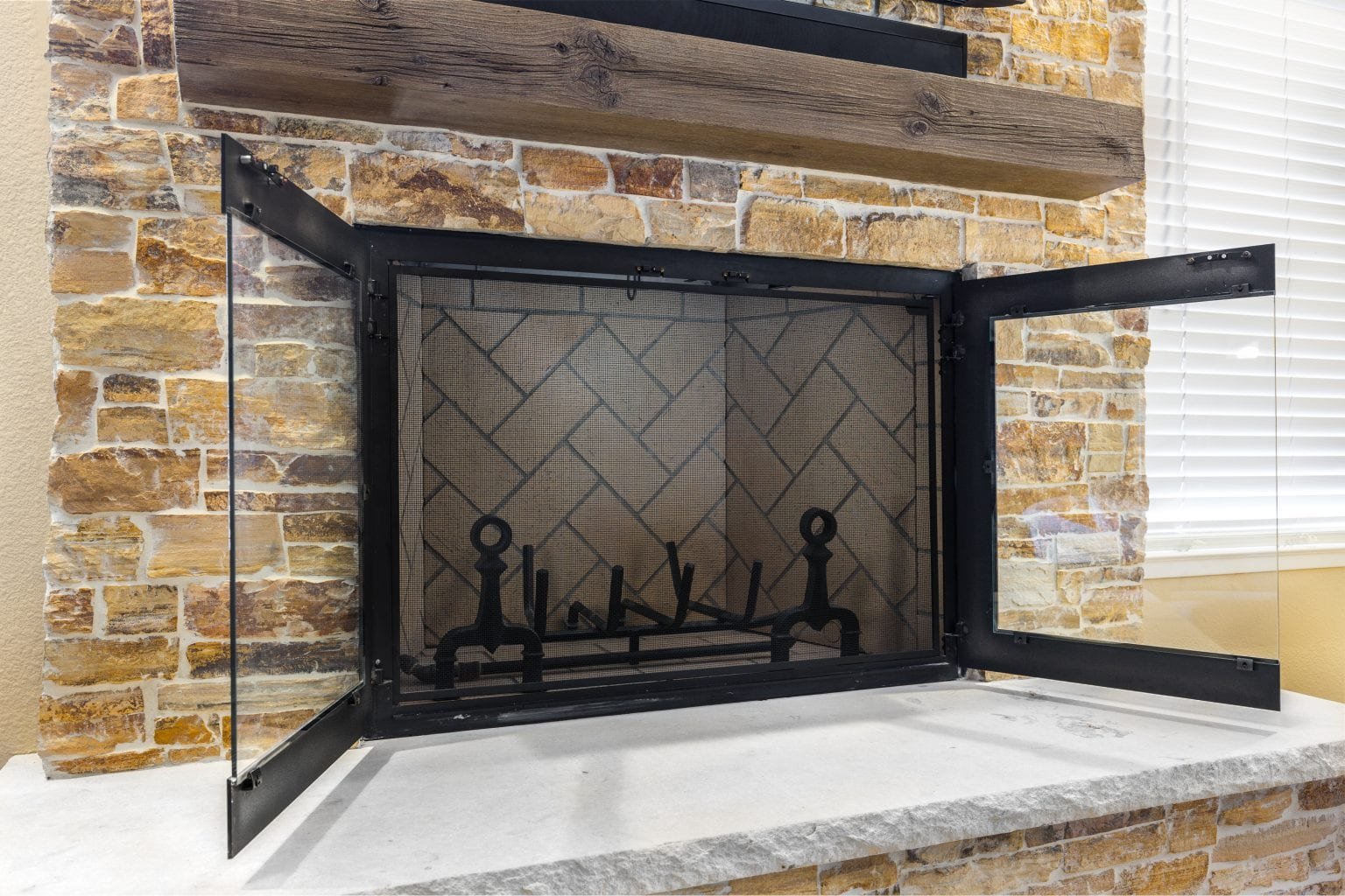 Stone fireplace with black mesh cover