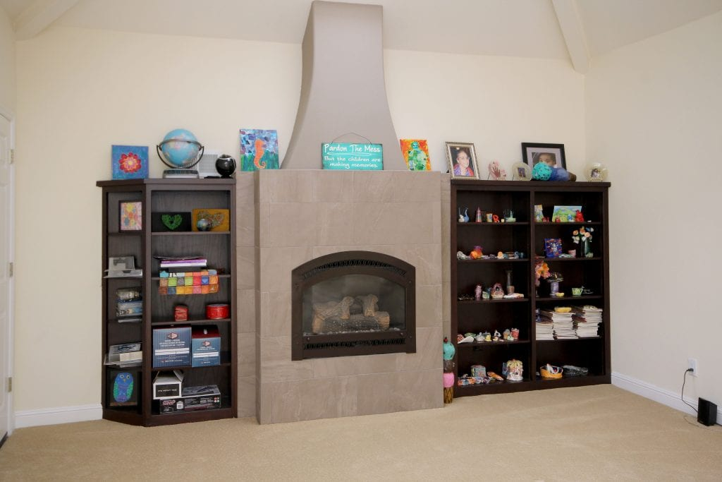 Built-in fireplace and surrounded by 2 black shelves