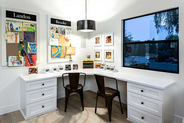 Home office with a white, L-shaped desk and 2 black chairs